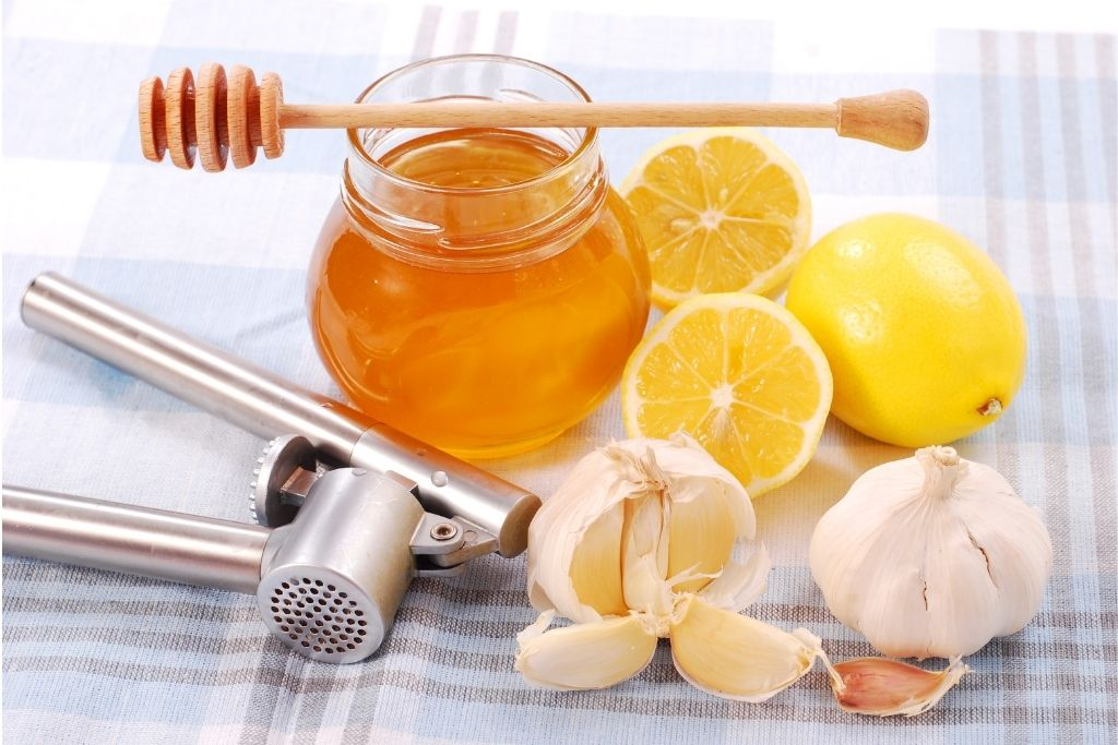 česnek s lisem na česnek, med ve sklenici a citron